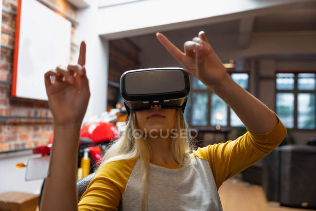 Self isolation in lockdown quarantine. front view of a young caucasian woman enjoying time at home, sitting in sitting room and using vr headset. — Stock Photo