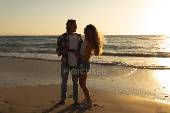 Coppia caucasica in piedi su una spiaggia durante un tramonto, che si tiene per mano, si abbraccia e si guarda — Foto stock