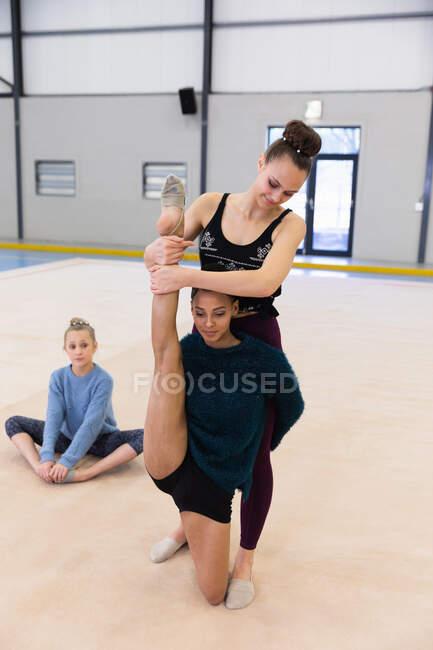 Вид спереди на одну смешанную расу и двух кавказских гимнасток-подростков, практикующихся в спортзале, одна девушка помогает другой размять ноги — стоковое фото
