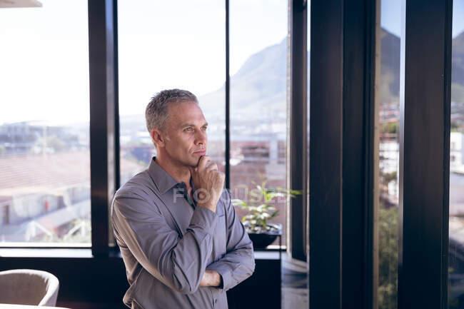 Кавказький бізнесмен, одягнений в сіру сорочку, працює в сучасному офісі, стоїть біля вікна, торкається підборіддя і думає в сонячний день. — стокове фото