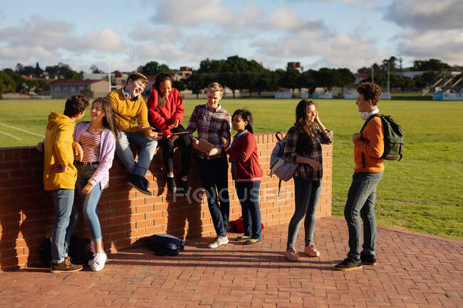 Front view of a multi-ethnic group of male and female teenagers with schoolbags hanging out and talking in their school grounds in sunlight — Stock Photo