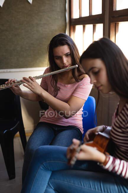 Vue de côté gros plan de deux adolescentes caucasiennes aux longs cheveux foncés assis devant une fenêtre jouant de la flûte et d'un ukulélé — Photo de stock