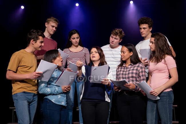 Vista frontale da vicino di un gruppo multietnico di coristi adolescenti di sesso maschile e femminile che tengono spartiti e cantano in piedi sul palco di un teatro scolastico durante le prove di uno spettacolo — Foto stock