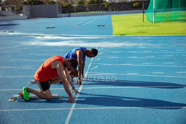 Вид сбоку кавказца и смешанной расы спортсмена, практикующего на спортивном стадионе, на позиции на стартовых блоках, готовящегося к спринту — стоковое фото