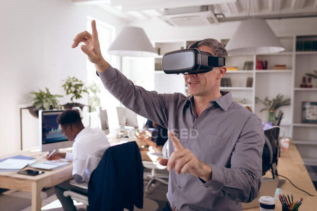 A Caucasian businessman working in a modern office, wearing VR headset, touching virtual interactive screen, with his business colleagues working at desks in the background — Stock Photo