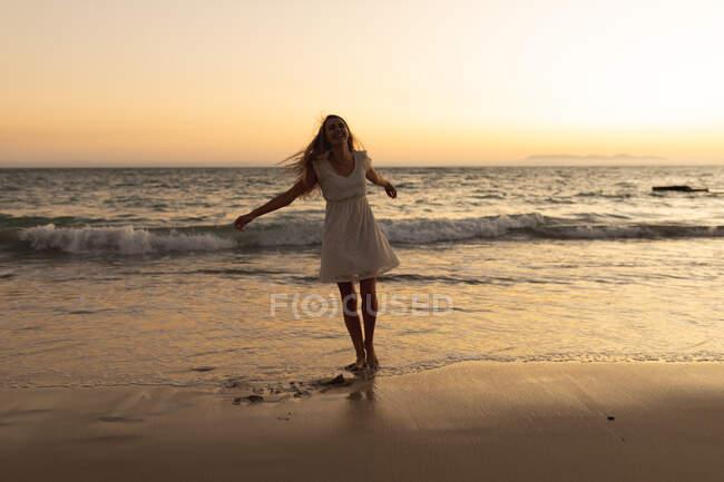Donna caucasica camminare a piedi nudi su una spiaggia durante il tramonto, giocare con la sabbia, guardando la fotocamera — Foto stock