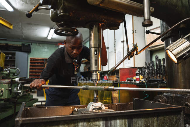 Работник афроамериканского завода в мастерской по изготовлению гидравлического оборудования, операционного оборудования. — стоковое фото