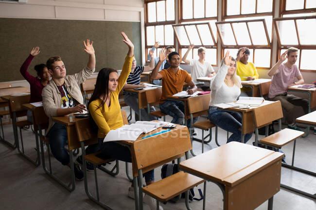 Vista lateral de un grupo multiétnico de adolescentes de secundaria en un aula escolar sentados en escritorios, todos levantando las manos para responder a una pregunta — Stock Photo