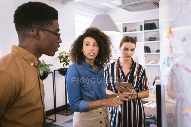 Мультиетнічна група колег по бізнесу чоловіків і жінок, які працюють в сучасному офісі, дивляться на дошку і розмовляють, одна жінка тримає планшетний комп'ютер — стокове фото