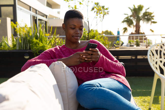 Front view of an African American woman hanging out on a roof terrace on a sunny day, sitting on a sofa, using a smartphone and smiling — Stock Photo