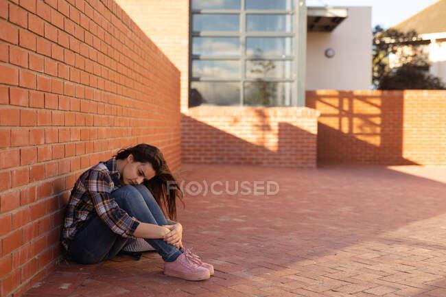 Seitenansicht eines traurigen kaukasischen Teenagers, der allein auf dem Schulhof einer High School sitzt — Stockfoto