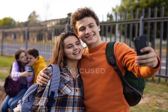 На переднем плане кавказская девочка-подросток и мальчик обнимаются и улыбаются, пока мальчик делает селфи с ними со смартфоном на территории школы, другая подростковая пара сидит на заднем плане — стоковое фото