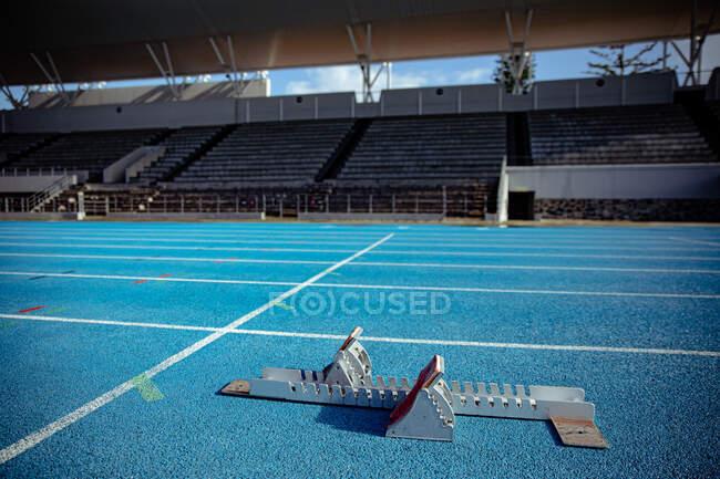 Крупный план стартовых блоков на гоночной трассе на спортивном стадионе, в солнечный день. — стоковое фото