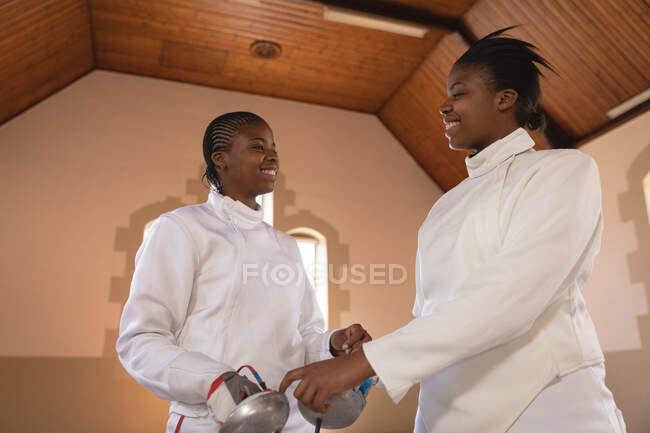 Desportistas afro-americanos vestindo roupa de esgrima protetora durante uma sessão de treinamento de esgrima, segurando epees e sorrindo. treinamento de esgrimistas em um ginásio. — Fotografia de Stock