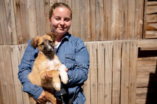 Vista frontal de uma voluntária em um abrigo de animais segurando um filhote de cachorro resgatado em seus braços em um dia ensolarado. — Fotografia de Stock