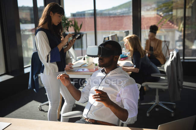 An African American businessman working in a modern office, wearing VR headset, touching virtual interactive screen, with his colleagues working in the background — Stock Photo