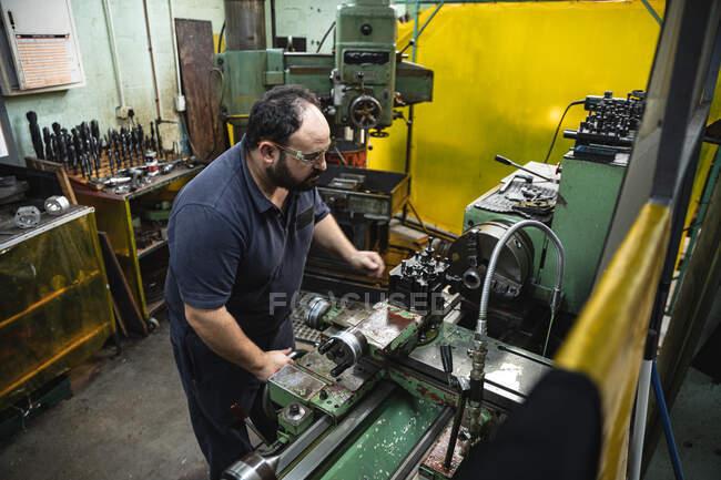 Кавказский работник завода в мастерской по изготовлению гидравлического оборудования, ношение защитных очков, операционное оборудование. — стоковое фото