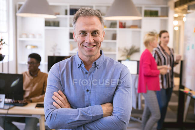 Portrait of a happy Caucasian businessman working in a modern office, looking at camera and smiling, with his business colleagues working in the background — Stock Photo