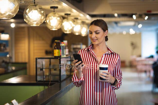 Кавказская деловая женщина с короткими волосами, стоящая в кафе, держа кофе на вынос и используя свой смартфон, одетая в модную одежду — стоковое фото