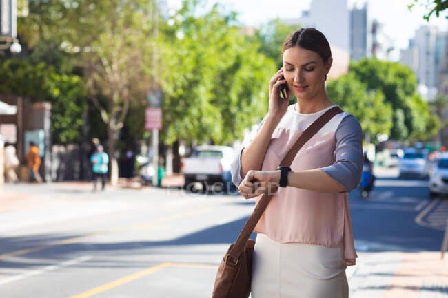 Кавказская деловая женщина в солнечный день, держит и разговаривает по смартфону, одетая в модную одежду и проверяет смартфоны — стоковое фото