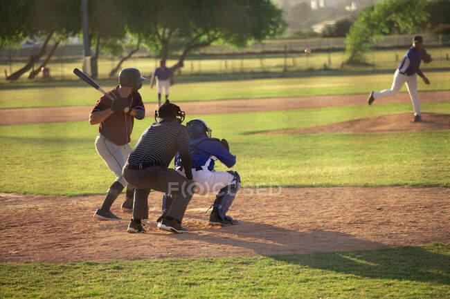 Вид сзади на белого бейсболиста во время игры в бейсбол в солнечный день, готовящегося ударить по мячу бейсбольной битой, кэтчер и другой игрок сидят на корточках за киллером — стоковое фото