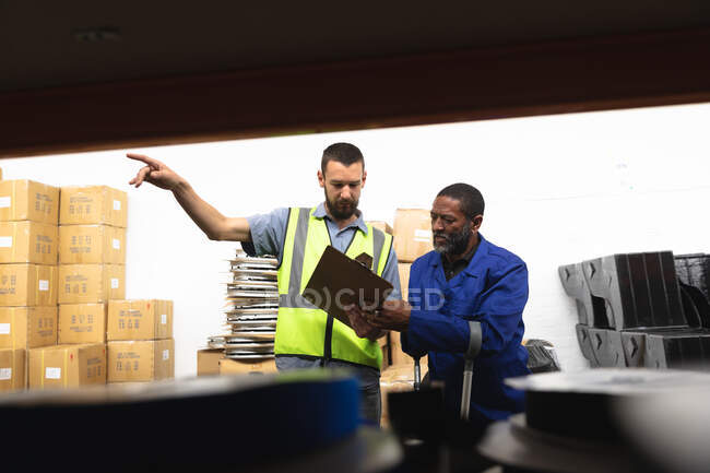 An African American male worker and a Caucasian male supervisor in a storage warehouse at a factory making wheelchairs, standing and talking, holding a clipboard — Stock Photo