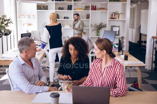 Мультиетнічна група чоловіків і жінок бізнес-колег, які працюють в сучасному офісі, сидять за столом, за допомогою ноутбука і планшета, обговорюючи свою роботу. — стокове фото