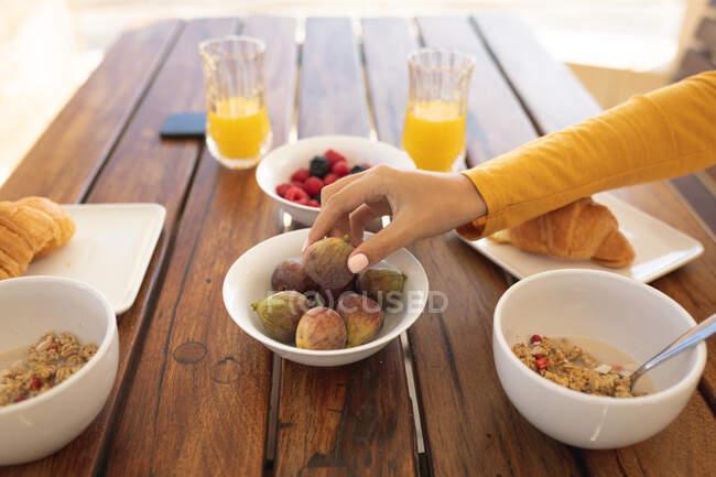 Женщина сидит за столом, завтракает, тянется за инжиром. Социальное дистанцирование и самоизоляция в карантинной изоляции. — стоковое фото