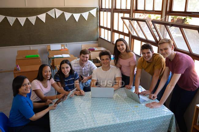 Vista de ángulo alto de un grupo multiétnico de alumnos adolescentes sentados y parados alrededor de una mesa en un aula usando computadoras portátiles y tabletas juntos en el momento del descanso mirando hacia la cámara y sonriendo - foto de stock