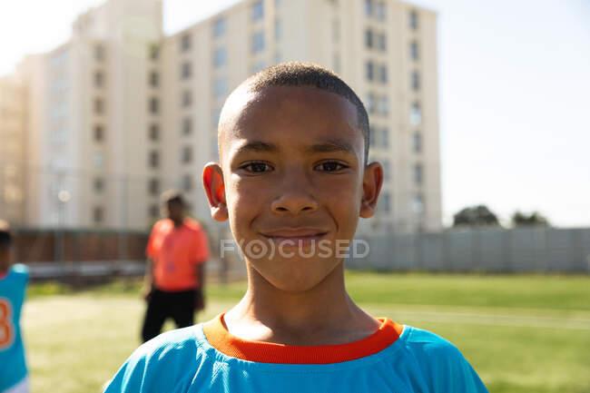 Портрет футболиста смешанной расы, одетого в синюю команду, стоящего на игровом поле в солнечный день, смотрящего в камеру и улыбающегося, с товарищами по команде, стоящими на заднем плане — стоковое фото