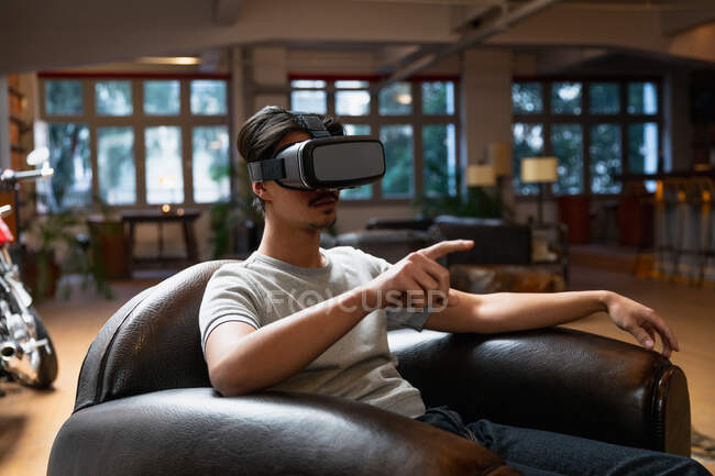 Side view of a young mixed race man enjoying time at home, sitting in sitting room and using VR headset. — Stock Photo