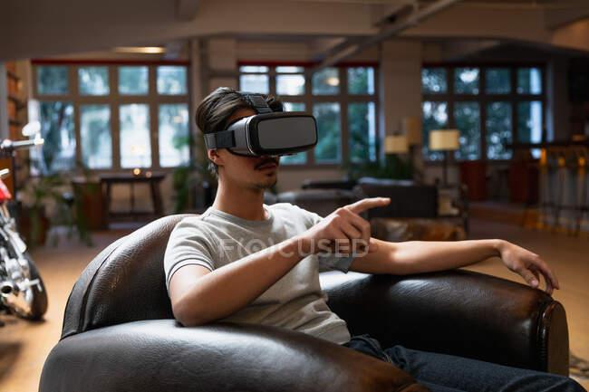Vista laterale di un giovane uomo di razza mista che si diverte a casa, si siede in salotto e utilizza cuffie VR. — Foto stock