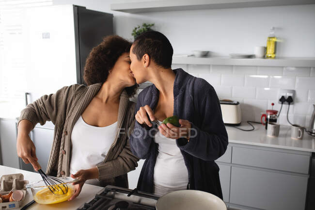 Front view of mixed race female couple relaxing at home, standing in the kitchen kissing while they prepare breakfast together — Stock Photo
