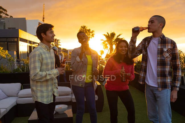 Vista frontal de un grupo multiétnico de amigos colgando en una terraza en la azotea con un cielo al atardecer, sosteniendo botellas de cerveza y bebiendo - foto de stock