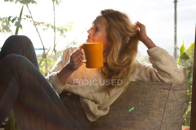 Vista laterale di una donna caucasica seduta nel suo salotto di fronte a una finestra in una giornata di sole, con una tazza e un sorriso — Foto stock