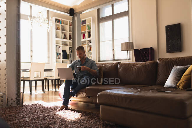 Front view of a young Caucasian man spending time at home, sitting on the sofa, using his laptop computer and holding a cup of hot beverage. — Stock Photo