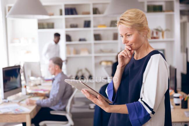 Кавказская деловая женщина, работающая в современном офисе, используя планшетный компьютер, держа подбородок и улыбаясь, со своим коллегой по бизнесу, работающим на заднем плане — стоковое фото
