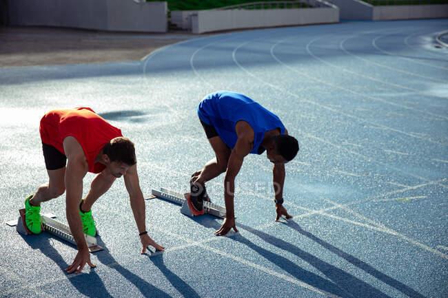Vue latérale d'un athlète caucasien et d'un athlète mixte pratiquant dans un stade sportif, en position sur les blocs de départ, se préparant au sprint — Photo de stock