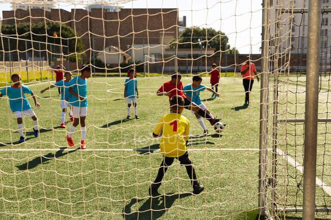 Vue arrière de deux équipes multiethniques de garçons joueurs de soccer portant leurs bandes d'équipe, en action lors d'un match de soccer sur un terrain de jeu, vu de derrière le but d'une équipe — Photo de stock