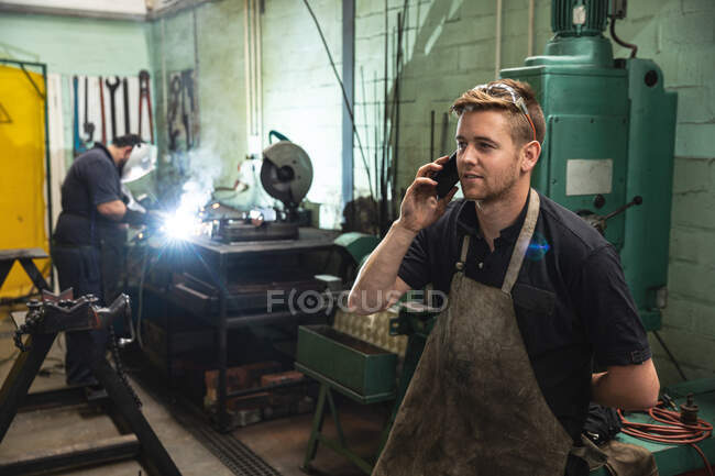 Caucasian male factory worker wearing apron talking on his smartphone with coworker welding in the background. Workers in industry at a factory making hydraulic equipment. — Stock Photo