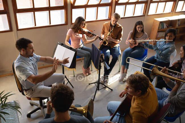 Vue latérale en angle élevé d'un enseignant caucasien assis dans une salle de classe conduisant un groupe multi-ethnique de musiciens adolescents masculins et féminins dans une pratique de la fanfare scolaire — Photo de stock