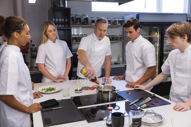 Kaukasische Gruppe männlicher und weiblicher Köche, die zuhören, wie ein leitender kaukasischer Koch Zutaten in einen Topf gibt. Kochkurs in einer Restaurantküche. — Stockfoto