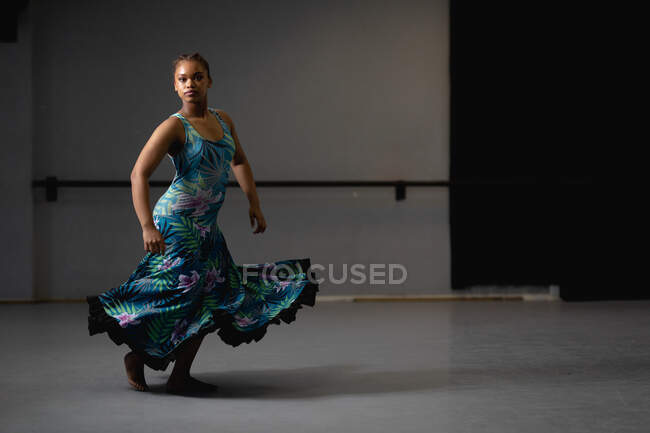 Front view of a mixed race female dancer wearing blue floral dress, dancing in a studio and looking straight into a camera. — Stock Photo