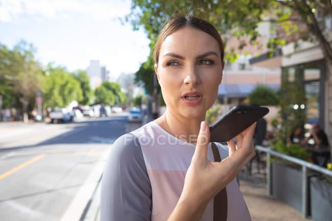 Кавказская деловая женщина в солнечный день звонит, держа смартфон перед собой. — стоковое фото