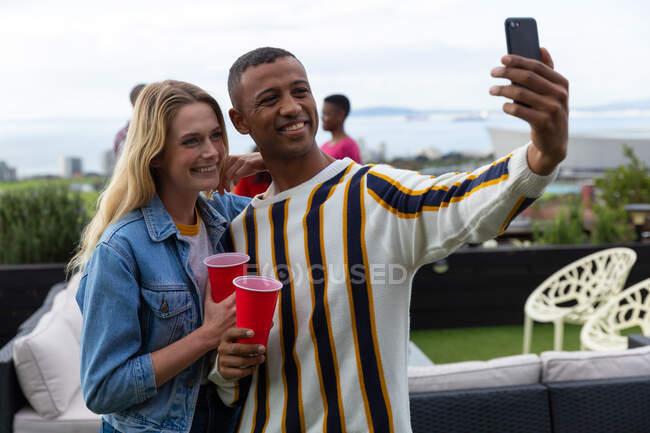 Vista frontal de una mujer caucásica y un hombre afroamericano pasando el rato en una terraza en un día soleado, tomando una selfie y sonriendo - foto de stock