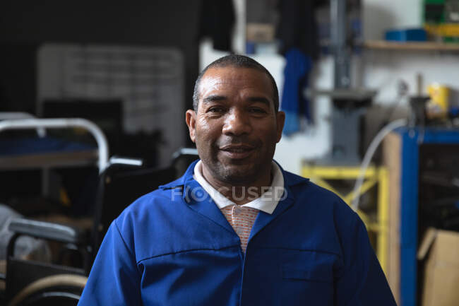 Portrait of a mixed race male worker wearing a workwear, in a storage warehouse at a factory making wheelchairs, looking at camera — Stock Photo