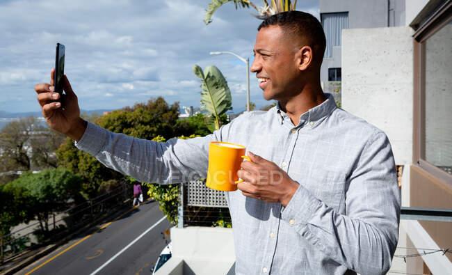 Вид сбоку на афроамериканца, болтающегося на балконе в солнечный день, делающего селфи, улыбающегося и держащего в руках кружку — стоковое фото