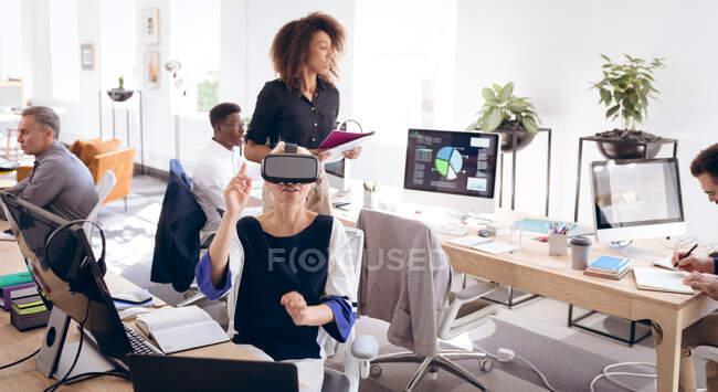 Кавказская деловая женщина, работающая в современном офисе, в VR гарнитуре, трогательная виртуальный интерактивный экран, со своими коллегами, работающими на заднем плане — стоковое фото