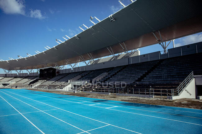 Вид трибун на спортивном стадионе с беговой дорожки, на ярком солнце с голубым небом на заднем плане — стоковое фото