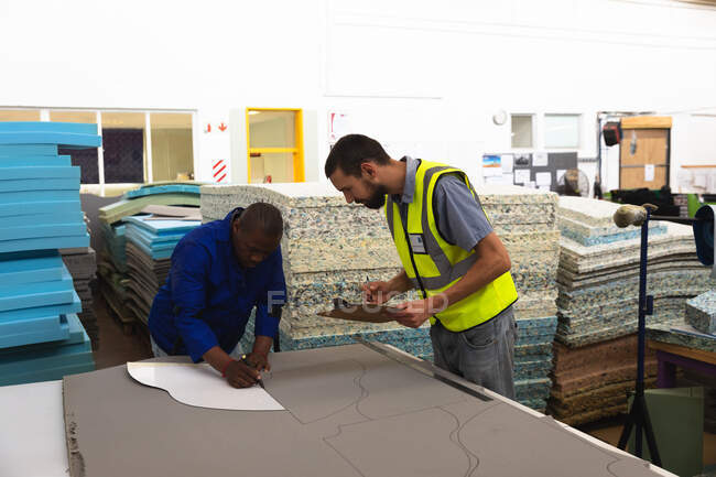 An African American male worker and a Caucasian male supervisor in a workshop at a factory making wheelchairs, the worker using a template on sheets of foam — Stock Photo